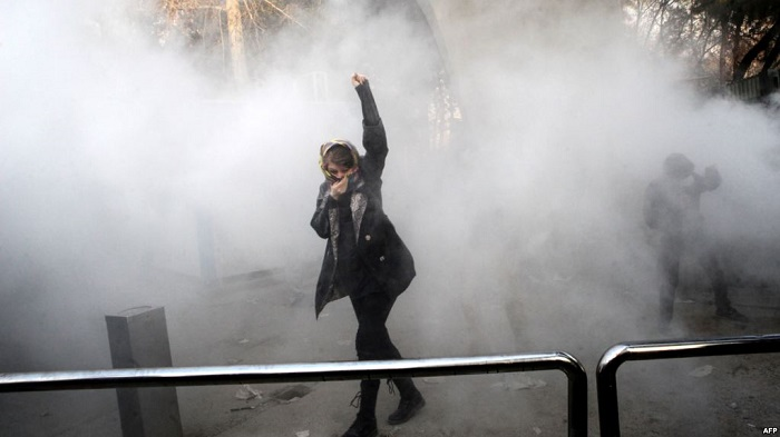 A student raises her arm in protest to the Iranian regime's repressive measures against peaceful protesters in Tehran-January 2018